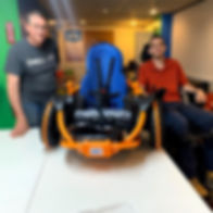 Two men pose for a photograph in a brightly colored room. The one in the red shirt sits in a wheelchair. On the tabletop between the two men is an orange and black chassis-like platform with big black wheels with an orange stripe. Set into this car-like platform is a blue seat with a high rounded back and safety belts.