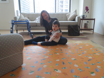 A small boy, Benny, is seated on the floor, being supported by an adult's arm.  The floor is painted orange, with flowers, like a patterned rug. A blue, pediatric-sized walker is nearby and behind them is a white sofa.