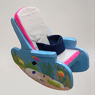 A cardboard chair has side panels that are curved at the base to form rockers, and are topped with armrests parallel to the floor.  The seat and backrest are padded with white-covered cushions with bright pink trim.  A wide belt is slotted through the cushion and backrest of the chair.  The chair itself is painted sea blue with an elaborate undersea scene.