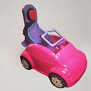 A child-sized toy car has been modified for 4-year-old Danna. A high back support, padded with yoga matting, holds a large red button at the top.  The lower part of the backrest curves around for her hips and trunk.  Attached to the steering wheel is a rectangle of tubing reaching toward the rear.  The car is hot pink; the modifications are pink and purple.