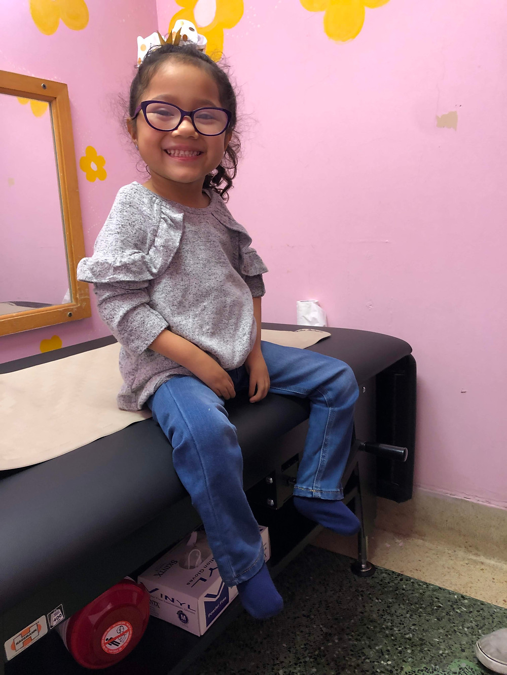 A little girl wearing glasses smiles for a picture as she sits on a long black cushioned table partly covered with brown paper. The room is painted light pink with bright yellow and white flowers. Behind the long table is a square brown mirror.