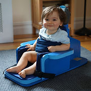 A small boy smiles as he sits in the blue floor chair, which is now fully upright on its base. His left arm rests on the armrest and his bare legs and feet reach almost to the end of the padded seat.  The child is secured by a wide blue torso belt.