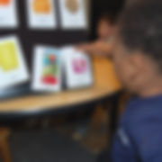 "A boy about 6 years old is facing mostly away from the camera, looking at 6 white cards, 4 x 6 inches each, arranged in 2 rows.  Each card has a 3-dimensional object partly embedded in it.  The boy is touching the card with the small yogurt cup, beneath which is a  label: ""yogurt.""  The other cards are ""juice"" (juice box),  ""drink"" (plastic cup),  ""cereal"" (cereal pieces encased in plastic),  ""muffin"" and ""food."" (The last two objects are obscured.)"