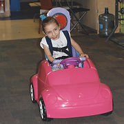 Little Danna is riding in the adapted toy car. The big button on the backrest is positioned right behind her head.  A series of black straps secure her trunk to the backrest.  Her hands grip the steering extension.