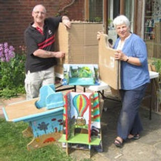 An older couple stands outdoors displaying various cardboard items, some brightly painted with scenes, and some unfinished.