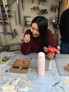 A girl with long black hair is smiling proudly at the blue tube switch in her right hand as she presses it to make a hand-held fan in her other hand spin around.  There are small  tools and a water bottle on the workbench in front of her; behind her are more tools on the wall.