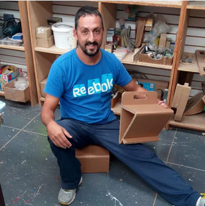 A bearded man in blue sits on a low cardboard box, one leg stretched out. He holds a wedge easel with a cutout for a handle and a lip at the front to hold papers in place.  Behind him are shelves with materials for building.