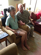 A couple in their sixties sit in their living room with their backs to a sunny window.  The woman, with short gray hair, sits upright in the modified armchair.  The lower curved support is visible as it wraps around her ribs on the right.  The higher support cradles the back of her head just below the crown.