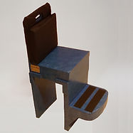 "An unusual looking chair has a backrest and seat, but no arms.  Instead of legs, it has two flat panels extending from the front and back of the seat to the floor.  On the front panel, about a foot from the floor, is a platform that protrudes about 10"".  A navy blue cushion covers most of the backrest, and two stripes of wide black tape run across the platform.  The whole chair is painted a glossy blue."