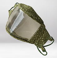 A face mask sits on a plain background.  Mask has a clear panel that makes the entire front of the mask transparent.  The rectangular panel is framed by green fabric patterned with pale stars.  Black cord attaches to the fabric panel on the side nearest the camera.