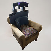 "An armchair upholstered in beige fabric has a patterned cushion added to the seat.  A rigid, flat backrest has been inserted in front of the chair back.  Attached to it is a sharply curved support at waist level, about 8"" high; it extends further around on the right side than the left.  At the top of the backrest is a sturdy U-shaped bracket holding another curved support."