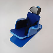 A blue cardboard chair with armrests is attached to a low platform.  The chair's seat and back are lined with dark blue yoga matting and tilted back about 30 degrees.  The slightly curved headrest and the sides of the chair are comfortably cushioned.
