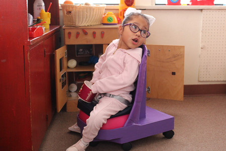 This little girl in pink sits on in the low purple seat with a hot-pink cushion. The wheels on the base are now plainly visible. Kaylee's feet rest easily on the floor.  Behind the child is a cupboard with its doors open.