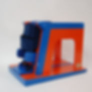 A red and blue open-sided box-like structure is new and shiny. It has a slightly wedge-shaped base.  At the high end of the wedge, two dark blue belts are slotted through the side of the box.  Below the belts, two rigid knee-level blocks protrude.  Beneath is a blue plate with more straps.