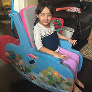 An 7-year-old girl sits in the rocking chair with arms extended to place her hands in her lap. Her head is reclined slightly against the cushioned backrest, which rises to just above her head.  The belt wraps snugly around her torso.  Her bare feet rest on the floor.