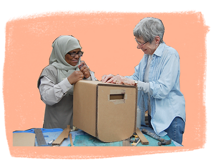 Two women are working on a boxlike seat with a slightly curved bottom. On the tabletop are a t-square and several cardboard strips.