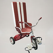 A red tricycle is fitted with a high-backed cardboard seat painted the same shade of red and decorated with two white racing stripes.  The seat has sloping sides several inches high.  The pedals have been built up with blocks and fitted with straps.