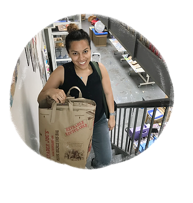 A young woman is standing on a staircase, smiling, and holding brown paper grocery store bags.  There are photographs on the wall beside her, and a lower floor with a workbench is behind her.