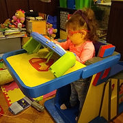 A small girl wearing glasses is secured in a colorful cardboard stander with an attached tray.  She is playing with a tabletop toy.  Her feet are safely held with dark blue straps.  Toys and books crowd the background.