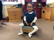 Kaylee sits in the seat with the rounded high back, which is now mounted on a platform at the right height so her feet just reach the floor.  A seat cushion has also been added.