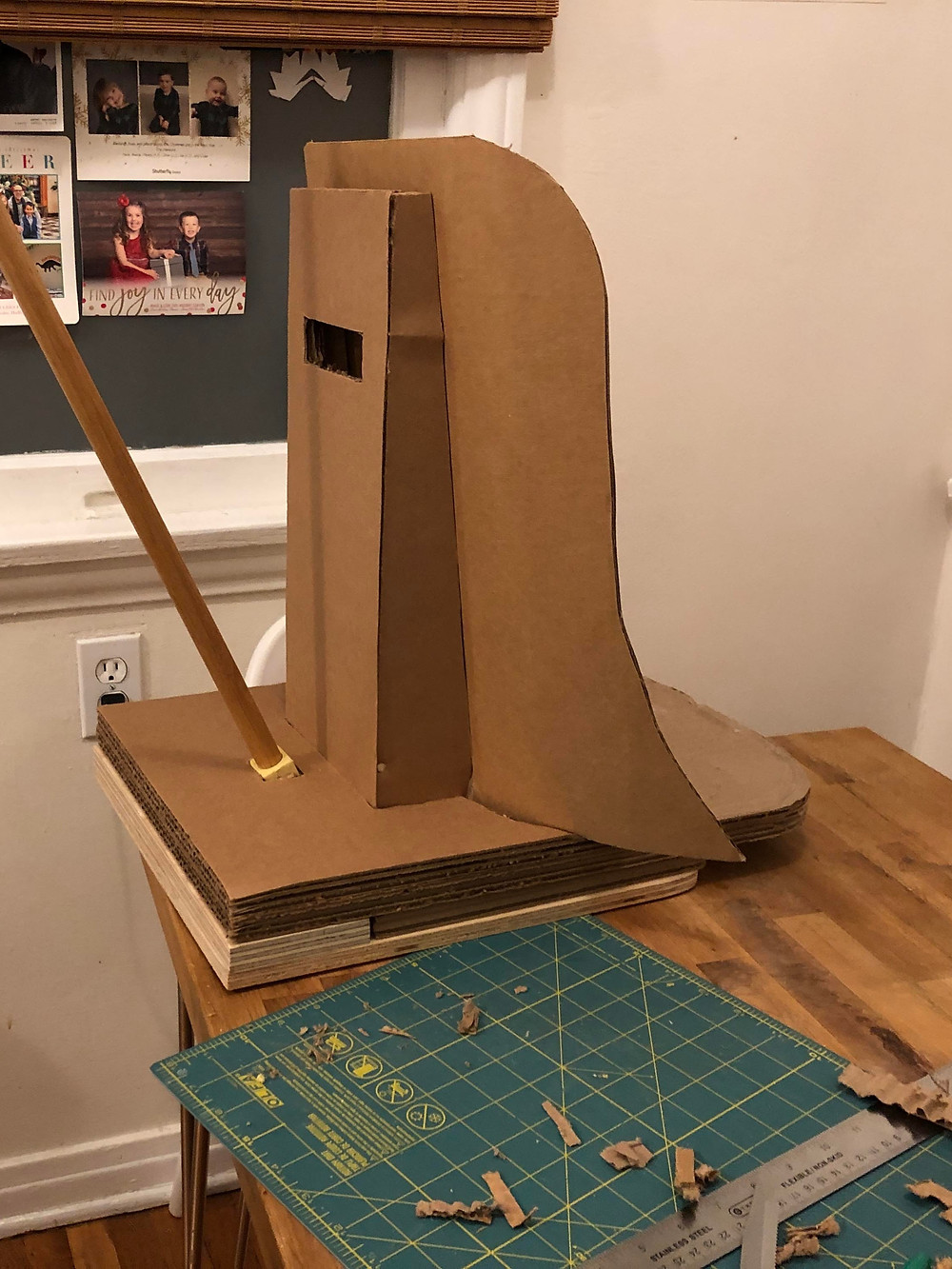 A work in progress, this cardboard seat has a rounded high back with slightly curved side pieces.  A pole is inserted into the platform behind the seat to be used to push the chair once wheels are added. A green cutting mat is on the workbench next to the seat.