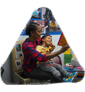 A woman reads to a little boy she is holding in her lap. The boy is smiling broadly as he looks at the book. Photos hang on the wall behind them.