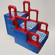 A set of three steps, each with a vertical red pvc handle at each end.   The top step is on a narrower base, though the handles are set into an extension on each side to make them the same width apart as the others.  The step unit is painted blue with red trim to match the handles.  The treads of the steps have a white spider web pattern painted on them.