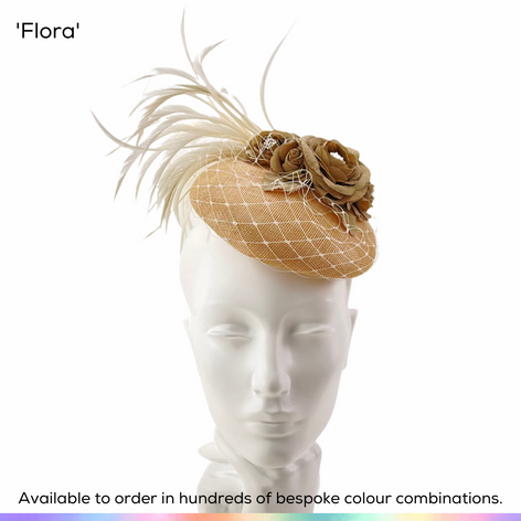 Flora.  Petite perching button shaped pillbox hat, layered with birdcage veiling and featuing a cluster of pretty garned roses.  A spray of bobbing biot feathers finishes the look.  Available to order in thousands of colour combinations to match your outfit perfectly.  Handmade by Marvellous Millinery, Winchester, Hampshire UK.  Bespoke ladies wedding hats for Mother of the Bride, Mother of the Groom, Top Table Wedding Guests, Ladies Day at Royal Ascot, Glorious Goodwood, Garden Parties at Buckingham Palace and Royal Investitures.