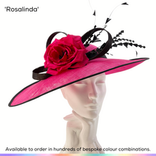 Rosalinda.  A generous east/west brim frames the face and hair, and the classic dome crown is accented with a beautiful handmade silk English rose in full bloom, highlighted with a graceful bow and spray of bobbing feathers.  Available to order in thousands of colour combinations to match your outfit perfectly.  Handmade by Marvellous Millinery, Winchester, Hampshire UK.  Bespoke ladies wedding hats for Mother of the Bride, Mother of the Groom, Top Table Wedding Guests, Ladies Day at Royal Ascot, Glorious Goodwood, Garden Parties at Buckingham Palace and Royal Investitures.