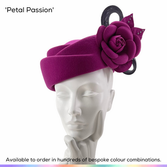 Petal Passion.  A gorgeous twist on a classic pillbox shape, this hat has a sculpted crown that resembles looking down onto a closed flower bud.  This detail has been echoed by the beautiful bloom that sits over one eye which has been accented with lines of crystals and a contrasting colour of sinamay bow to the rear.  Available to order in thousands of colour combinations to match your outfit perfectly.  Handmade by Marvellous Millinery, Winchester, Hampshire UK.  Bespoke ladies wedding hats for Mother of the Bride, Mother of the Groom, Top Table Wedding Guests, Ladies Day at Royal Ascot, Glorious Goodwood, Garden Parties at Buckingham Palace and Royal Investitures.