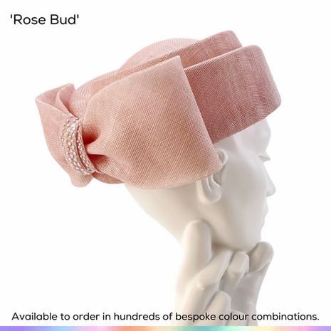 Rose Bud.  Charming sculpted full-sized pillbox hat, shaped to look like a rose bud from above.  Featurng a gathered sinamay bow tot he rear, with a cinch that has been decorated with crystal accents.  Available to order in thousands of colour combinations to match your outfit perfectly.  Handmade by Marvellous Millinery, Winchester, Hampshire UK.  Bespoke ladies wedding hats for Mother of the Bride, Mother of the Groom, Top Table Wedding Guests, Ladies Day at Royal Ascot, Glorious Goodwood, Garden Parties at Buckingham Palace and Royal Investitures.