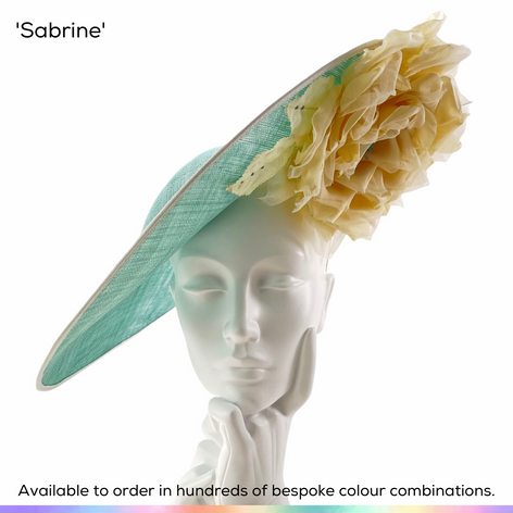 Sabrine.  A very stylish oversized slice saucer style headpiece, featuring a dramatic handmade silk rose in full bloom, set with crystals and supprted by a bow to the rear.  Available to order in thousands of colour combinations to match your outfit perfectly.  Handmade by Marvellous Millinery, Winchester, Hampshire UK.  Bespoke ladies wedding hats for Mother of the Bride, Mother of the Groom, Top Table Wedding Guests, Ladies Day at Royal Ascot, Glorious Goodwood, Garden Parties at Buckingham Palace and Royal Investitures.