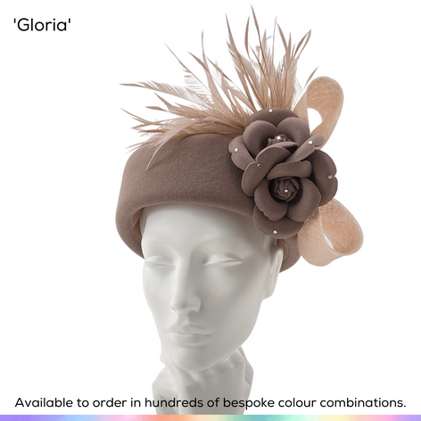 Gloria.  A classic pillbox shaped hat as made famous in the 60s, and shown here with a pair of stylised camellia flowers and a spray of bobbing biot feathers, framed beautifully by a stylish bow to the rear.  Available to order in thousands of colour combinations to match your outfit perfectly.  Handmade by Marvellous Millinery, Winchester, Hampshire UK.  Bespoke ladies wedding hats for Mother of the Bride, Mother of the Groom, Top Table Wedding Guests, Ladies Day at Royal Ascot, Glorious Goodwood, Garden Parties at Buckingham Palace and Royal Investitures.