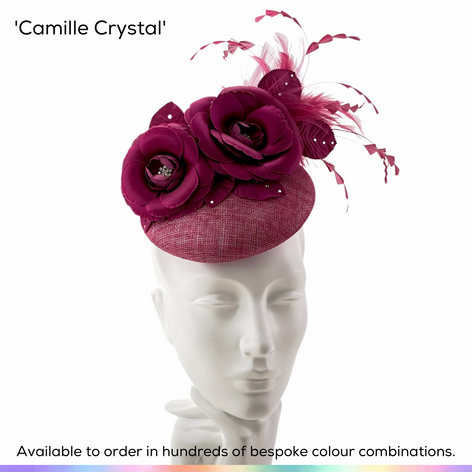 Camille Crystal.  An entrancing petite button shaped pillbox hat featuring a pair of stunning camellias in silk satin.  A spray of bobbing feathers frame the face perfectly.  Available to order in thousands of colour combinations to match your outfit perfectly.  Handmade by Marvellous Millinery, Winchester, Hampshire UK.  Bespoke ladies wedding hats for Mother of the Bride, Mother of the Groom, Top Table Wedding Guests, Ladies Day at Royal Ascot, Glorious Goodwood, Garden Parties at Buckingham Palace and Royal Investitures.