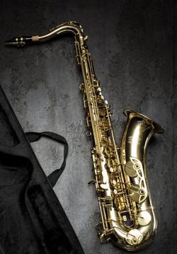 brass-saxophone-on-gray-table-near-black