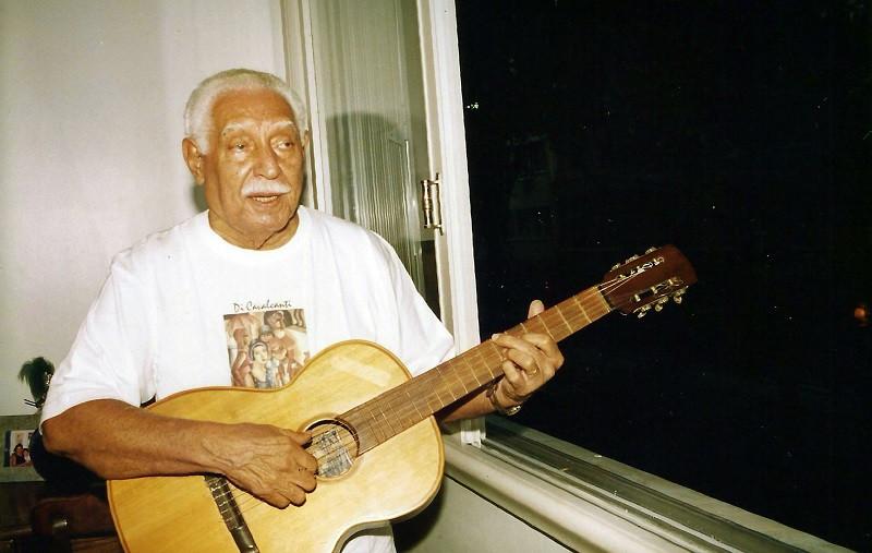 Dorival Caymmi tocando violão na janela de seu apartamento, em Copacabana