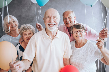 Smiling elderly man and his friends with balloons enjoying his birthday party.jpg