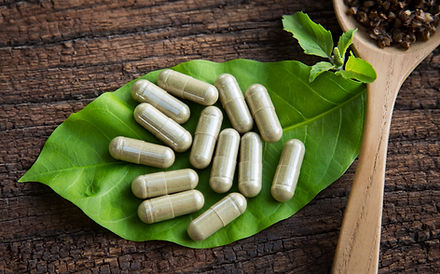 Herbal medicine in capsules with holy basil on green leaf with wooden spoon .jpg