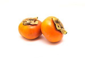 Two ripe Fuyu persimmon isolated on whit