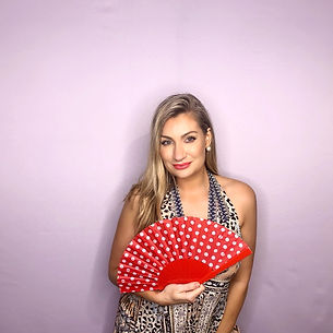 A woman posing with red fan in front of pink backdrop Booth Chic Brisbane Photo Booth