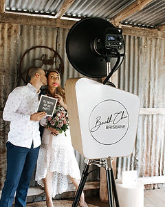 Husband and wife posing in a photo booth