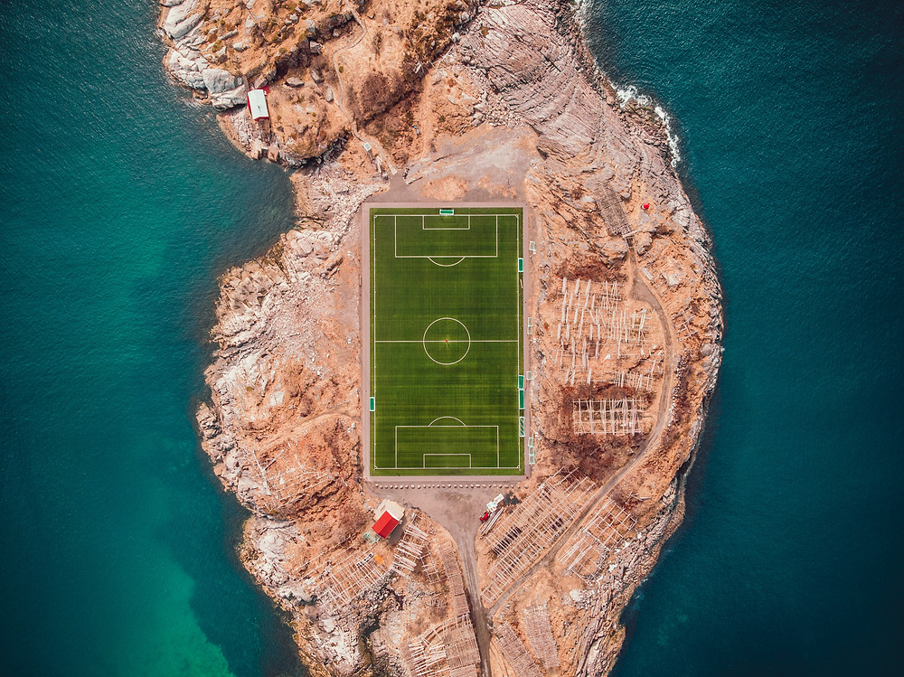 A clearly lined soccer field created within chaotic, unpredictable natural rock formations.