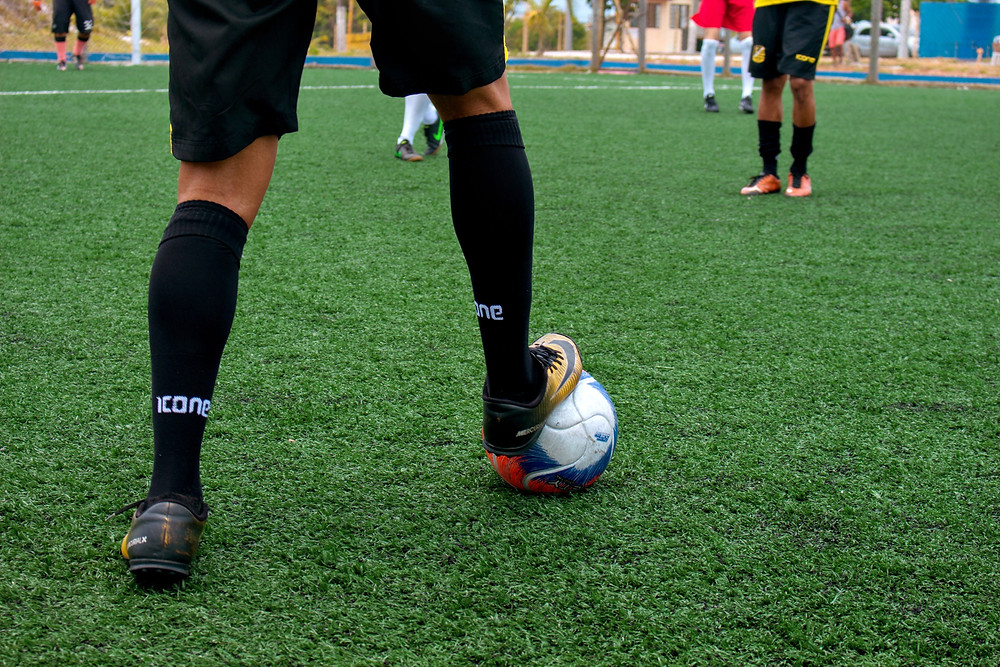 soccer player with ball at their feet, waiting to make a play; just as those with Deliberative talents pause to assess risk.