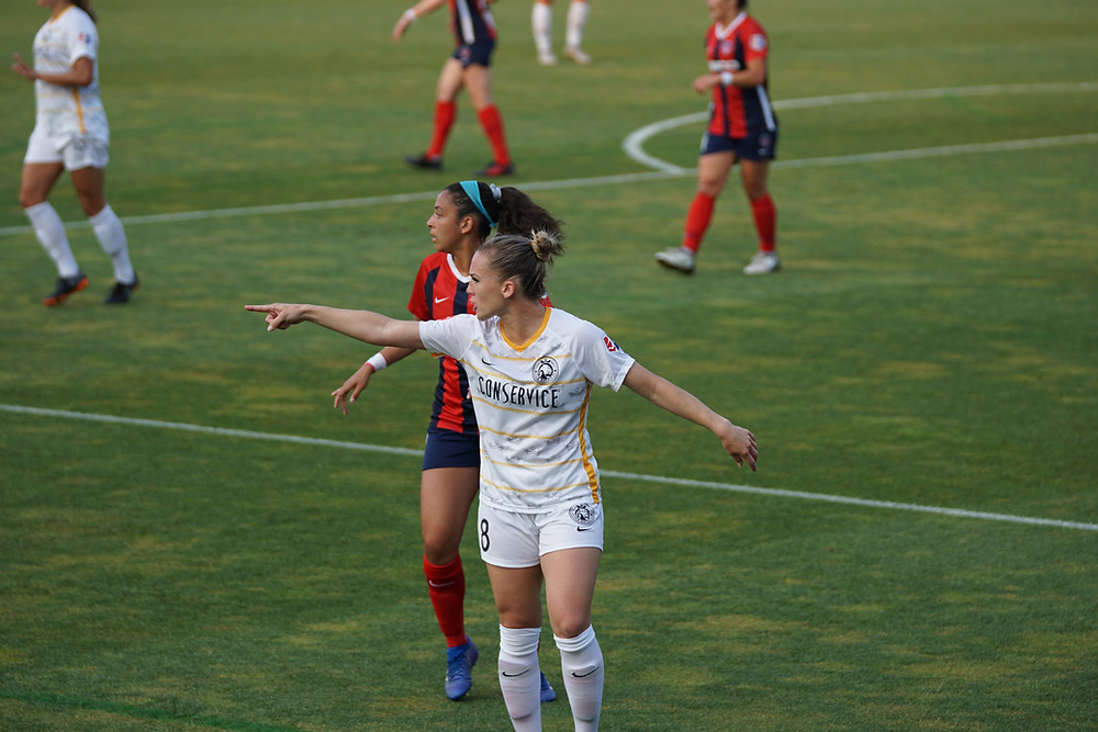 A soccer player pointing to communicate a change on the field.