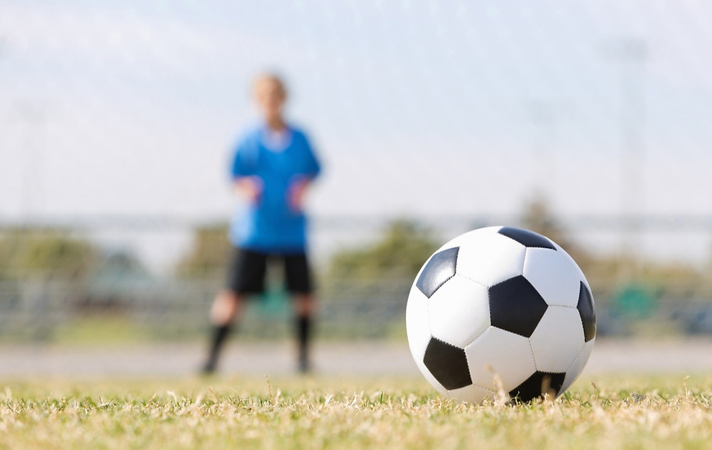 A ball right before the goal with the focus on the ball; the only thing that matters is the ball.