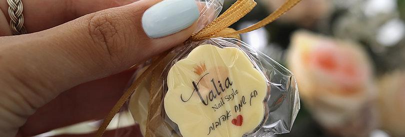פרליני שוקולד ממותגים בצלופן וסרט סאטן