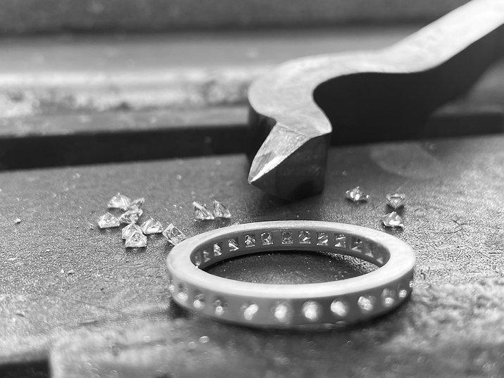 Witgouden alliance ring ingezoomd op de binnenkant. De binnenkant van ring is voor de diamanten afgwerkt met een vierkanten stalen pons.