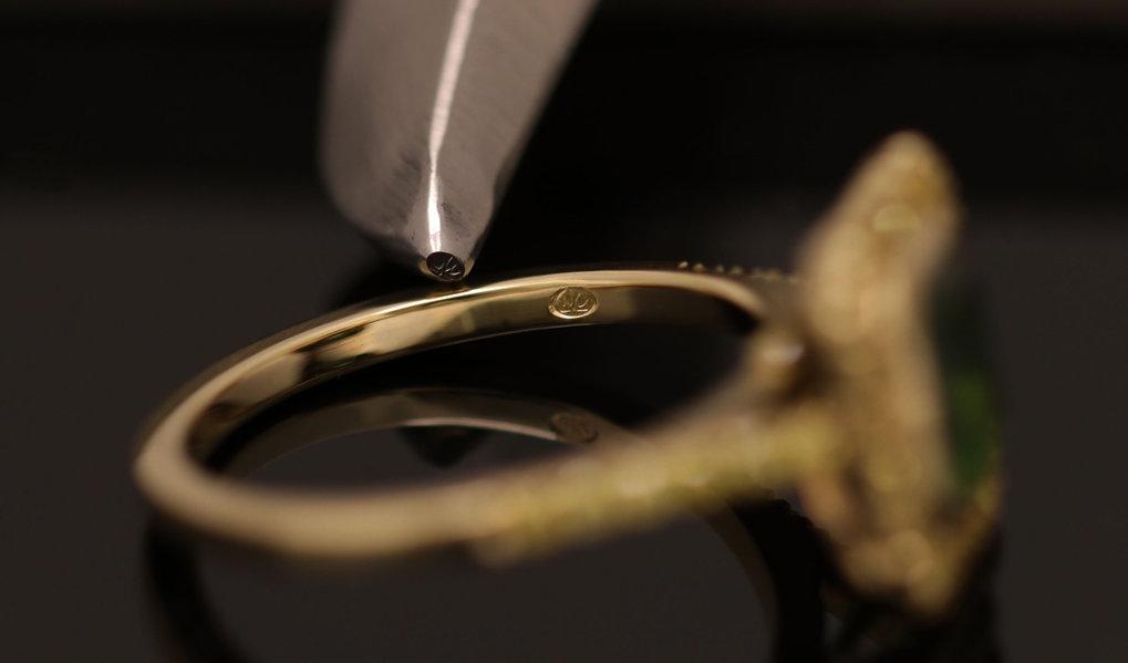 Stempel afdruk van het logo WV-goudsmid ingeslagen in een geelgouden ring.