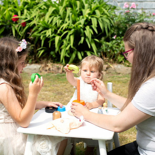 bridesmaids and nanny playing with stacking toy.jpg