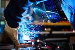 Técnico soldando parte del montaje de un compresor en cisterna de cemento